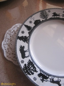 Piring bermotif pohon Natal dan binatang. Latar putih dan gambar hitam bikin kesan elegan dan simpel.